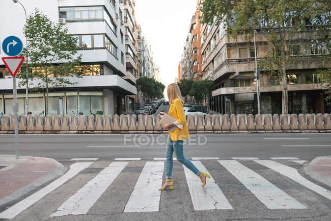 Вид сбоку на трехлетнюю стройную женщину в элегантной ярко-желтой куртке и джинсах с цифровым планшетом, идущую в одиночестве по пешеходному переходу на фоне выходов из жилых многоэтажек и припаркованных на улице в центре города автомобилей — стоковое фото