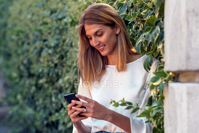 Positive relaxed blonde female in casual clothes focusing on screen and smiling while standing on street and interacting with smartphone near fence covered green climbing plant — Stock Photo
