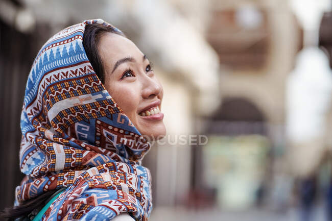 Jovem mulher étnica no lenço de cabeça sorrindo e olhando para longe, enquanto está contra o fundo urbano borrado na cidade de Jeddah, na Arábia Saudita — Fotografia de Stock