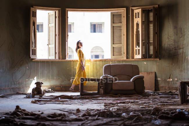 Vista lateral de la joven mujer étnica vestida de amarillo que se encuentra cerca de la ventana abierta en la habitación desordenada de la antigua casa deshabitada con restos de muebles y basura en el suelo. - foto de stock