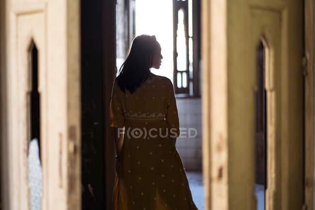 Rückansicht einer jungen ethnischen Frau in Kleid, die in der Tür gegen Fenster in einem alten Steinhaus steht — Stockfoto
