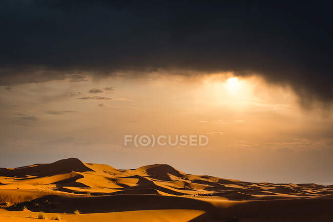 Spectacular landscape of desert with sand dunes with dramatic cloudy sunset — Stock Photo
