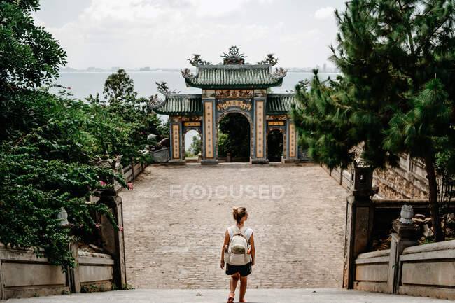 From above side view of delighted female traveler with backpack strolling in tropical garden near religious temple and enjoying majestic landscape — Stock Photo