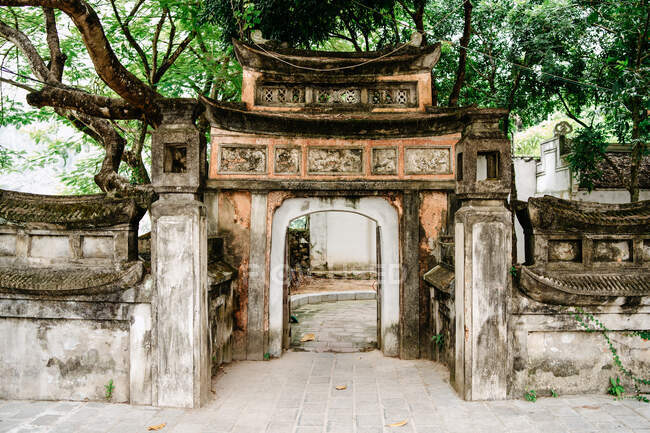 Exterior of stone arch entrance of old temple surrounded by tall trees in courtyard — Stock Photo