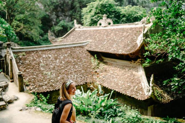 Сверху вид восхитительной женщины-путешественницы с рюкзаком прогуливаясь в тропическом саду рядом с религиозным храмом и наслаждаясь величественным пейзажем — стоковое фото