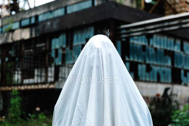 Невпізнавана людина рука покрита білим ліжком лист маскується як привид з сільськими металевими конструкціями на задньому плані — стокове фото
