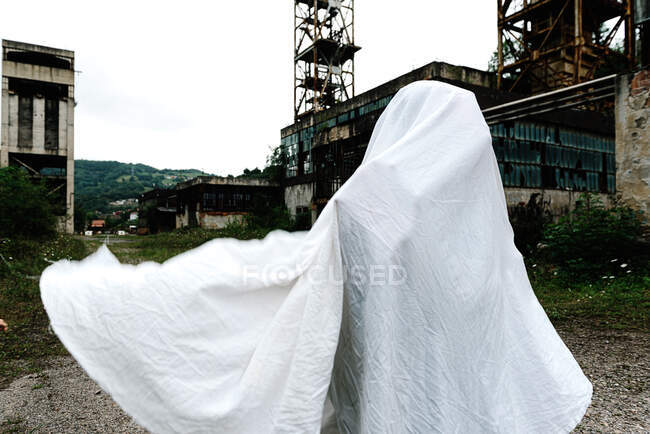Unrecognizable person hand covered in white bed sheet masked as ghost with rustic metal constructions on background — Stock Photo