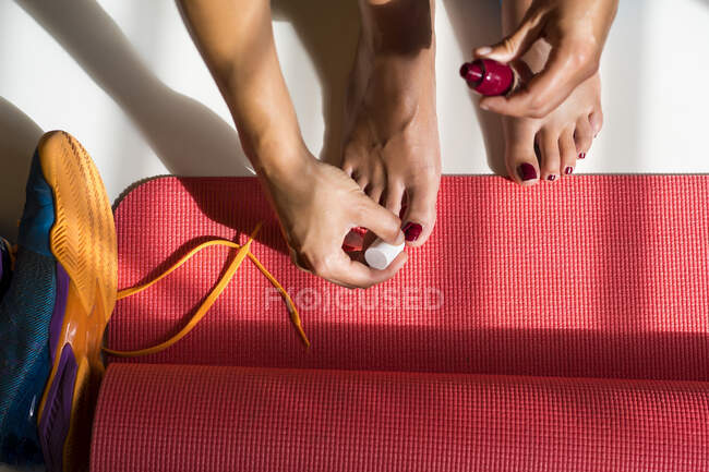 From above of crop anonymous female making pedicure and applying nail polish on yoga mat near running shoes at home — Stock Photo