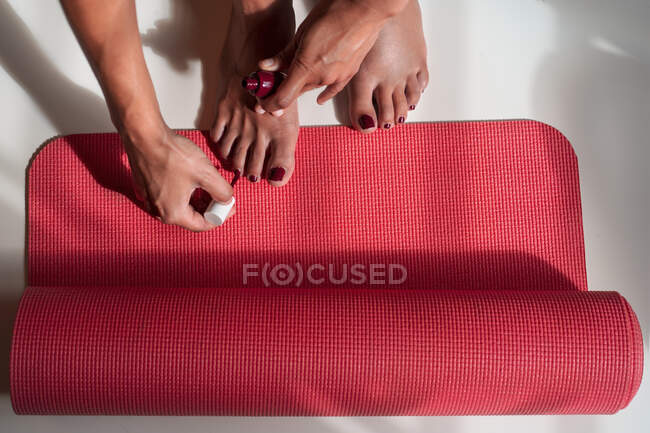 Desde arriba de la cosecha femenina anónima haciendo pedicura y aplicando esmalte de uñas en la esterilla de yoga en casa - foto de stock