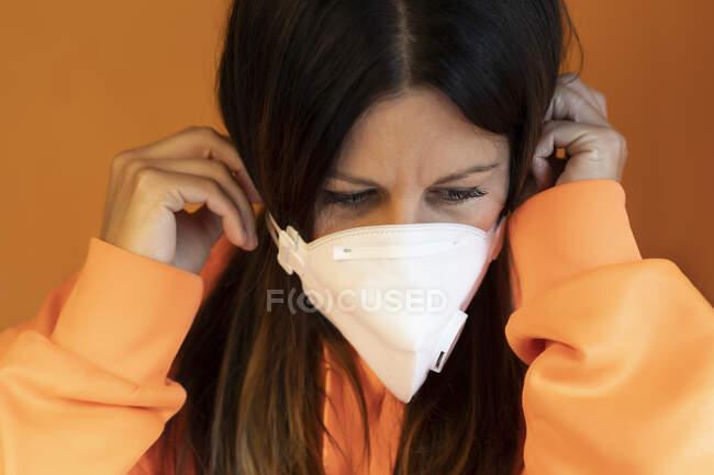 Jovem fêmea em jaqueta laranja casual colocando máscara protetora branca contra fundo laranja — Fotografia de Stock