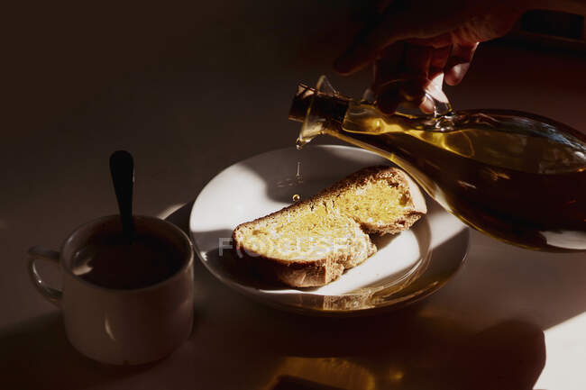 From above crop anonymous person pouring olive oil from bottle on bread toast placed on table near mug of hot drink while preparing breakfast at home — Stock Photo