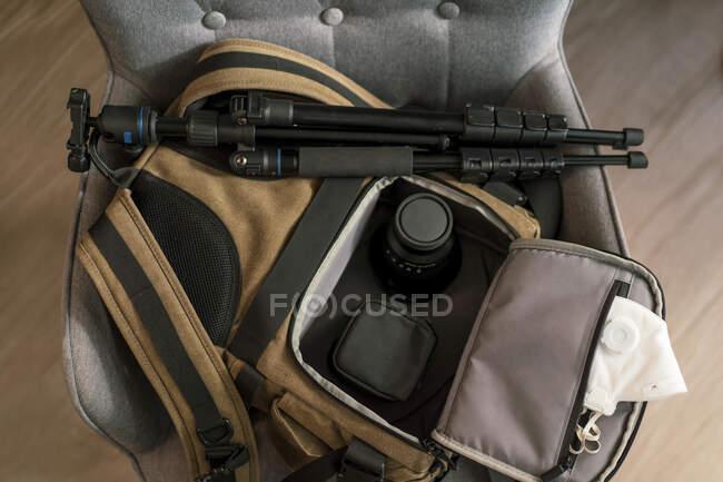 Draufsicht auf Tasche mit modernem Fotozubehör und weißer Atemschutzmaske auf Stuhl im Zimmer — Stockfoto