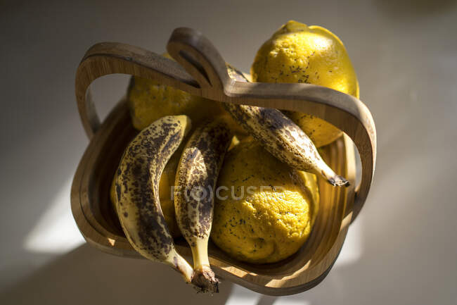 From above of fresh ripe bananas and lemons in wooden basket placed on table in light kitchen — Stock Photo