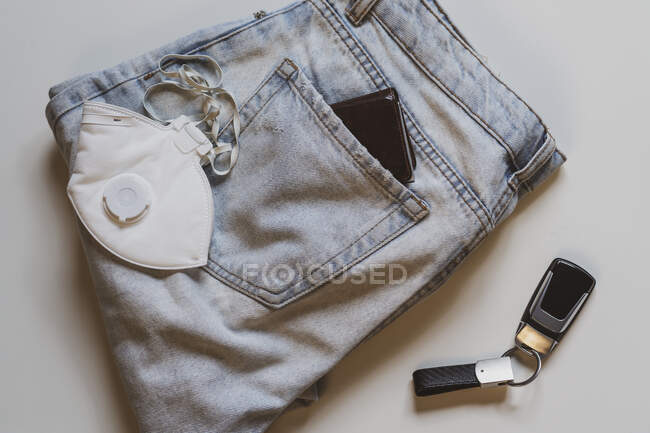 From above of folded jeans with white protective mask in pocket and car keys placed on white background in light studio — Stock Photo