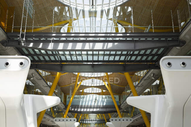 International airport with metal baggage claim area and massive constructions in futuristic style lit by sunlight — Stock Photo