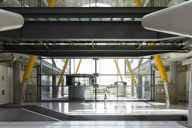 Задній вид дитини стоїть у просторий термінал міжнародного аеропорту в футуристичному стилі і дивиться у вікно, очікуючи вильоту. — стокове фото