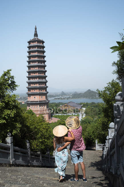 Back view of couple in love wearing conical hats walking along bridge towards tall tower of Buddhist pagoda during summer holiday — Stock Photo