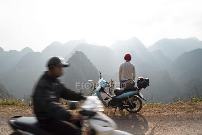 Male biker near motorcycle enjoying mountainous landscape — Stock Photo