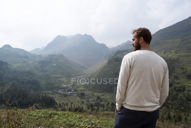 Back view of traveling male in casual outfit standing on green hill and enjoying scenic view of mountain peaks during foggy morning — Stock Photo