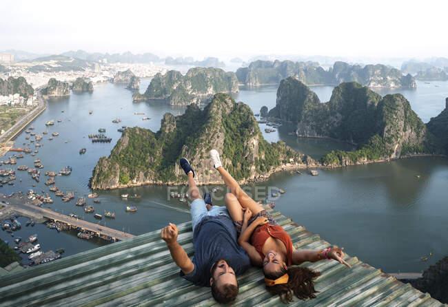 Desde arriba vista superior de pareja amorosa acostada en el techo de metal y observando pintoresca vista de la bahía de Halong en Vietnam - foto de stock