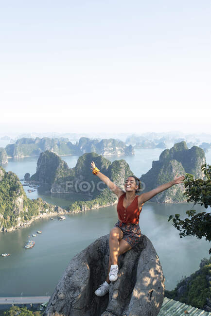 From above of delighted traveling woman sitting on rock with closed eyes and outstretched arms while enjoying summer holiday on background of spectacular scenery of Halong bay — Stock Photo