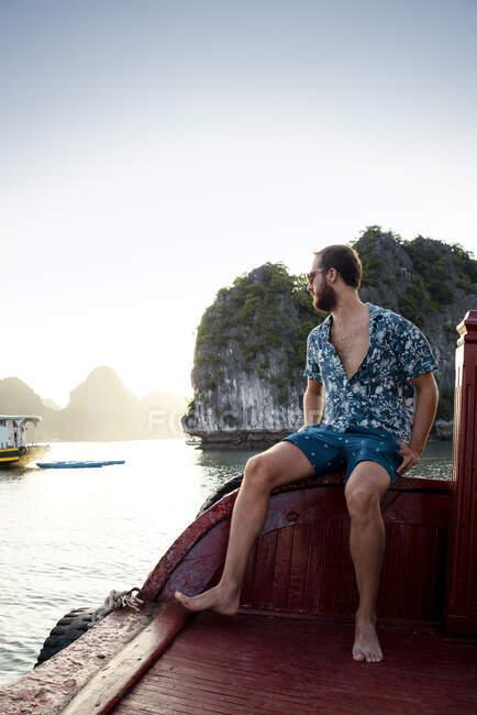 Vue latérale du mâle voyageur en tenue décontractée reposant sur un quai en bois et admirant des paysages étonnants d'eau et de montagnes tranquilles — Photo de stock