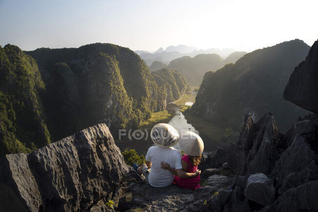 From above back view of couple of tourists in conical hats hugging while sitting on high rocky top of Mua cave and admiring magnificent tropical valley in ridges — Stock Photo