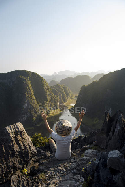 From above back view of anonymous male tourist with open arms on rocky terrain in Mua cave and observing spectacular scenery during vacation — Stock Photo