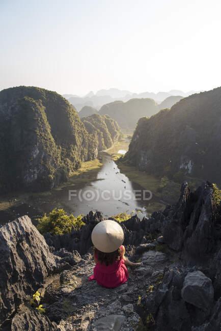 Desde arriba vista trasera de turista femenina anónima relajándose en terreno rocoso en la cueva de Mua y observando paisajes espectaculares durante las vacaciones - foto de stock
