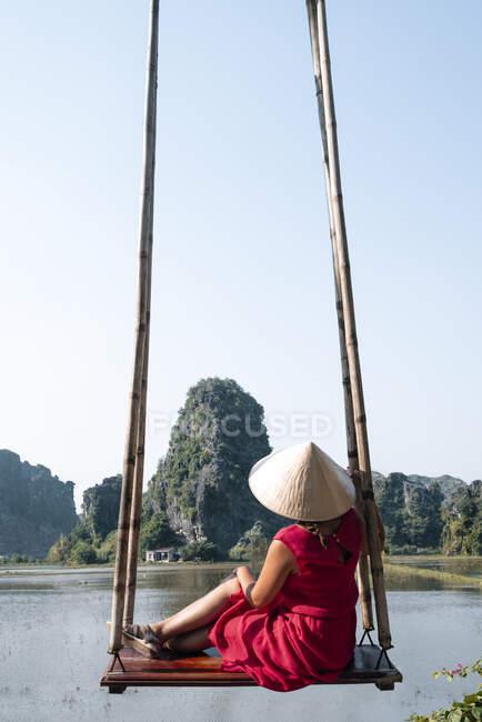 Vista trasera de una turista femenina irreconocible con ropa casual y sombrero cónico sentado en un columpio de madera y admirando el increíble paisaje de rocas en el agua - foto de stock