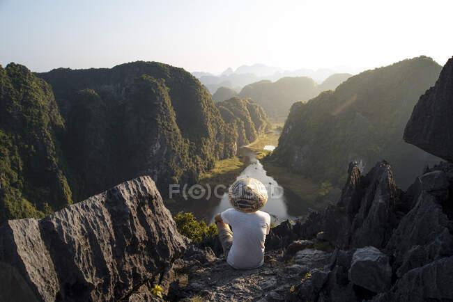 Desde arriba vista trasera del turista masculino anónimo relajándose en terreno rocoso en la cueva de Mua y observando paisajes espectaculares durante las vacaciones - foto de stock
