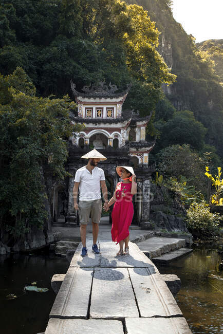 Couple of tourists in conical hats walking on stone bridge leading to shabby oriental archway while enjoying vacation and looking at each other — Stock Photo