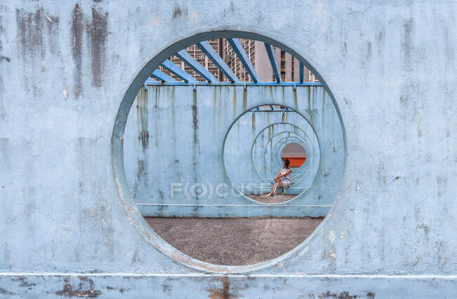 Female in summer dress sitting on concrete base of unusual city installation in shape of passage with round holes and looking away — Stock Photo