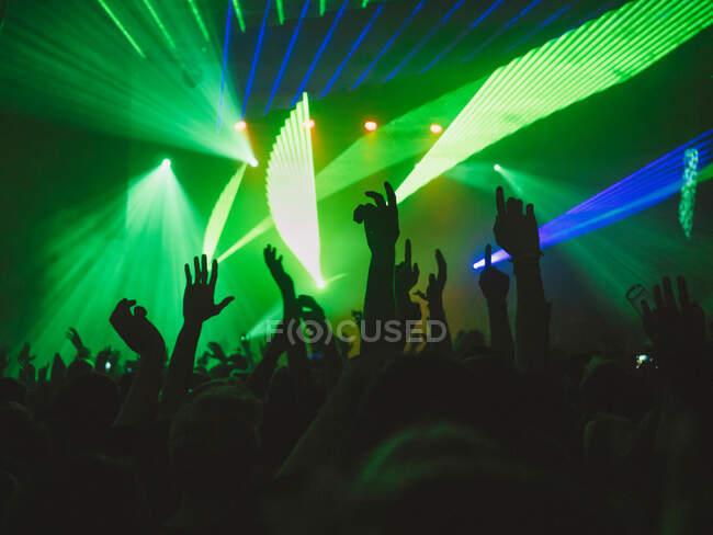 Retrovisore sagome di persone contro illuminato con luci palcoscenico durante la performance musicale — Foto stock