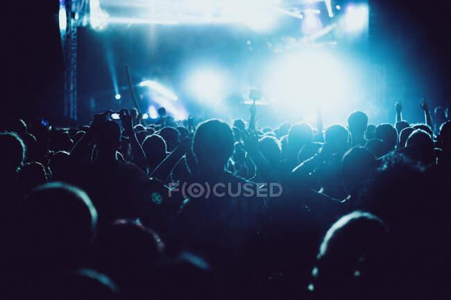 Rückansicht Silhouetten von Menschen gegen Beleuchtung mit Lichtern Bühne während der Musik-Performance — Stockfoto
