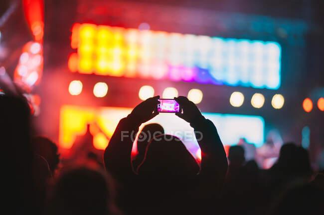 La silhouette della vista posteriore di una persona irriconoscibile che scatta video con smartphone mentre guarda lo spettacolo moderno contro il palco illuminato al neon — Foto stock