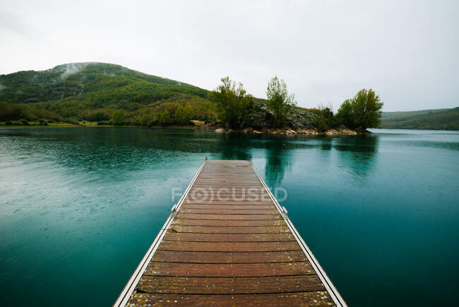 Landscape with wooden planked footway in calm lake water against forest — Stock Photo
