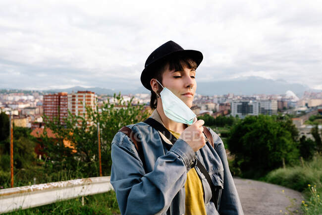Serious young lady in casual clothes and hat standing with medical mask on street with eyes closed and enjoying fresh air during walk being on quarantine — Stock Photo