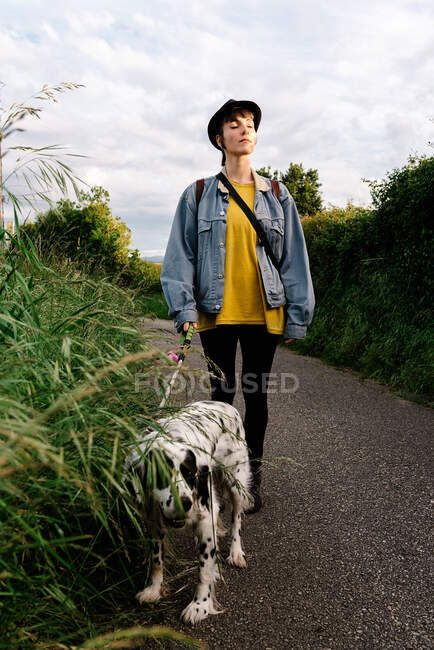 Joven dama positiva con ropa casual y sombrero negro de pie con los ojos cerrados en camino asfaltado durante el paseo con perro cerca de hierba verde. - foto de stock