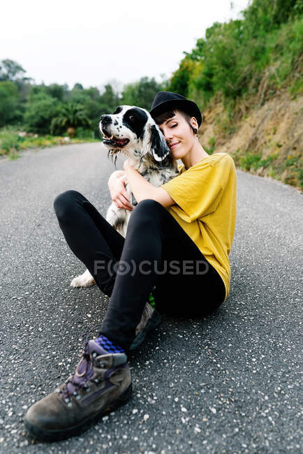 Cheerful young lady in casual clothes and hat sitting on ground with her dog during walk on street — Stock Photo