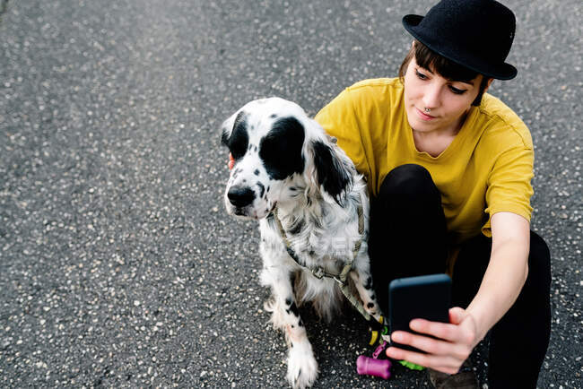 Young lady in casual clothes and hat sitting on ground with mobile phone and taking selfie with dog during walk on street — Stock Photo