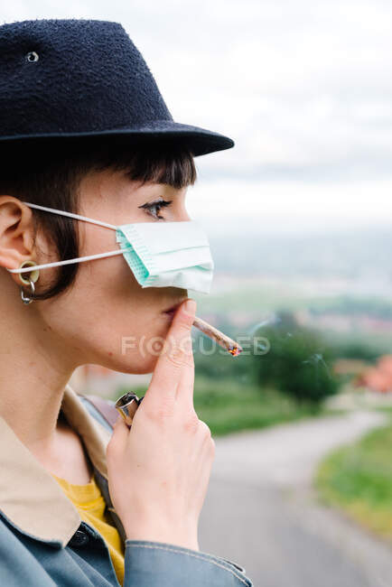 Side view of young lady in casual clothes and hat wearing medical mask on nose and smoking cigarette while standing on street — Stock Photo