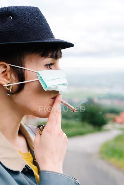 Seitenansicht einer jungen Frau in Freizeitkleidung und Hut, die eine medizinische Maske auf der Nase trägt und Zigarette raucht, während sie auf der Straße steht — Stockfoto
