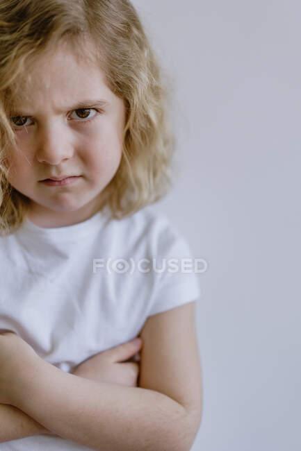 Розчарована дитина в повсякденній футболці дивиться на фотоапарат на білому фоні в студії — стокове фото