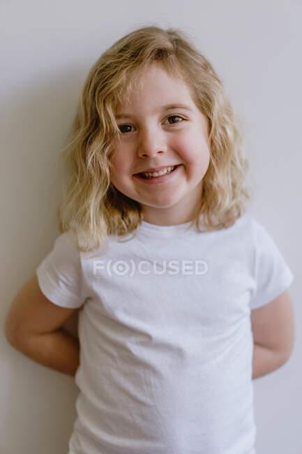 Niño positivo vistiendo ropa casual sonriendo y mirando a la cámara mientras está de pie y apoyado en la pared blanca en el estudio moderno - foto de stock