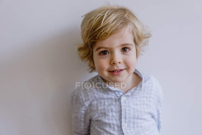 Adorable content child in casual shirt standing near while wall and smiling while looking at camera — Stock Photo