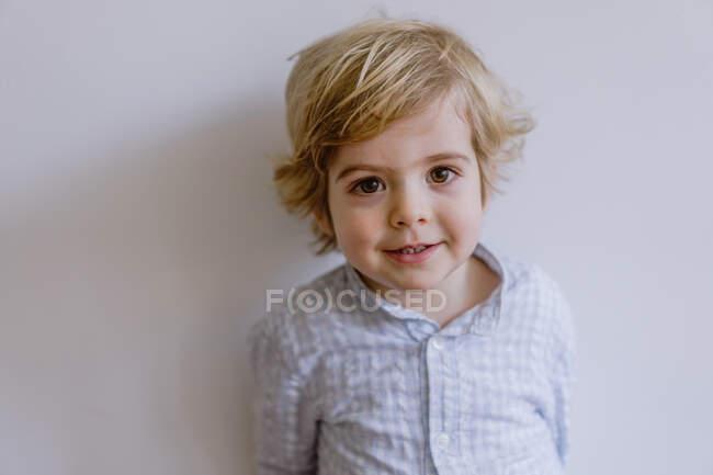 Niño contenido adorable en camisa casual de pie cerca de la pared y sonriendo mientras mira la cámara - foto de stock