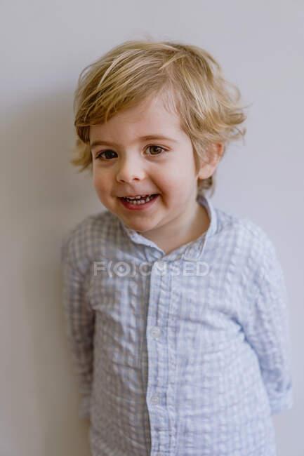 Criança adorável vestindo camisa casual sorrindo e olhando para a câmera no fundo branco do estúdio — Fotografia de Stock