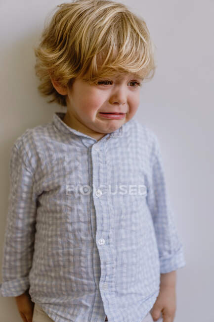 Разочарованный маленький ребенок в повседневной рубашке стоял возле белой стены и плакал на белом фоне в студии — стоковое фото