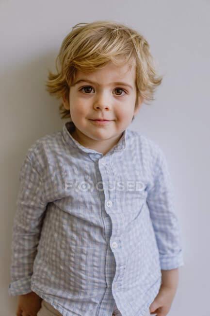 Adorabile bambino che indossa camicia casual sorridente e guardando la fotocamera su sfondo bianco dello studio — Foto stock